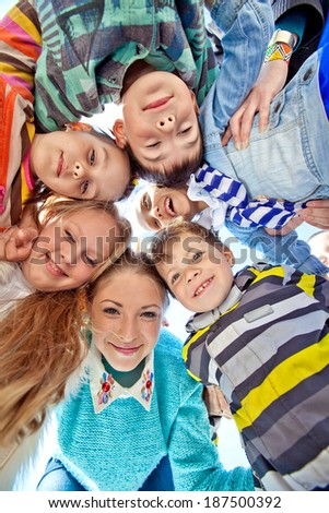 Happy friends looking down and holding hands - stock photo