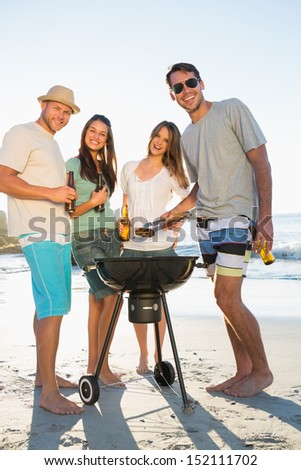 Happy friends on the beach looking at camera while having barbecue together - stock photo