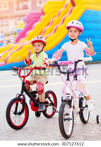 Happy friends on the bicycles, brother with sister having fun in amusement park, gesturing peace by hands, playing game outdoors, enjoying friendship and summer holidays - stock photo