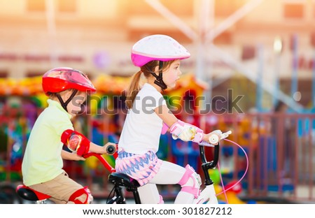 Happy friends on the bicycles, brother with sister having fun in amusement park, playing game outdoors, enjoying friendship and summer holidays - stock photo