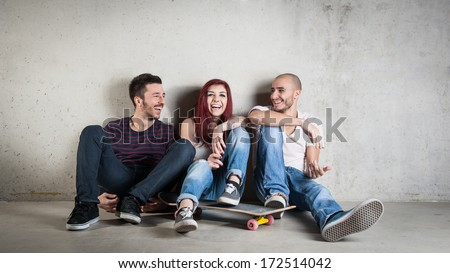 Happy friends portrait with skateboard against concrete wall.  - stock photo