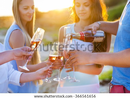 Happy friends pouring champagne sparkling wine into glasses outdoors at a beach. Sunset beach party