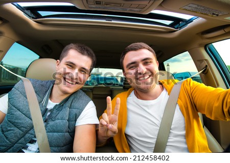 Happy friends ready for vacations driving car - stock photo