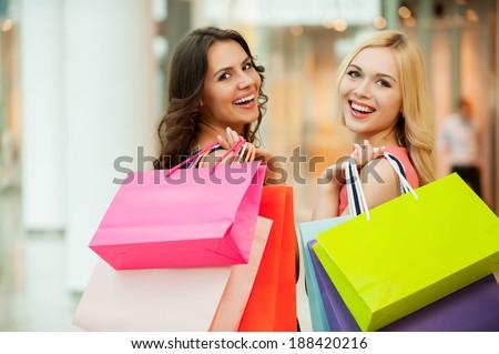 Happy friends shopping. Two beautiful young women enjoying shopping at shopping mall - stock photo