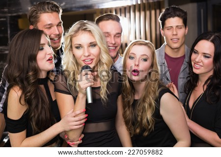 Happy friends singing karaoke together at the bar - stock photo