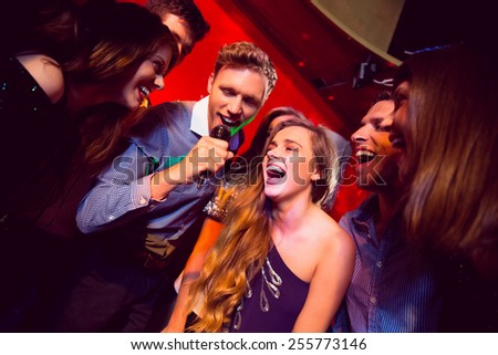 Happy friends singing karaoke together at the nightclub - stock photo