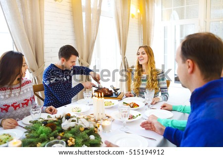 Happy friends sitting around a table and enjoying Christmas dinner together