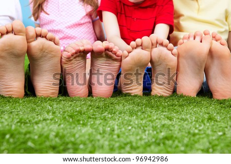 Happy friends sitting on the grass barefoot - stock photo