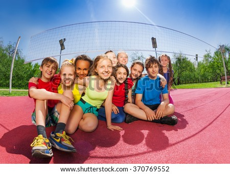 Happy friends sitting on the volleyball game court - stock photo