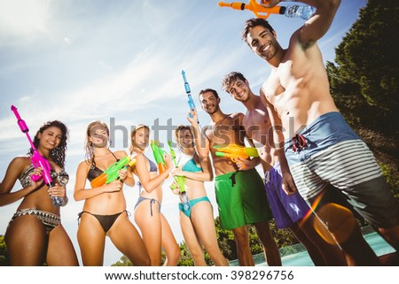 Happy friends standing with water guns near swimming pool
