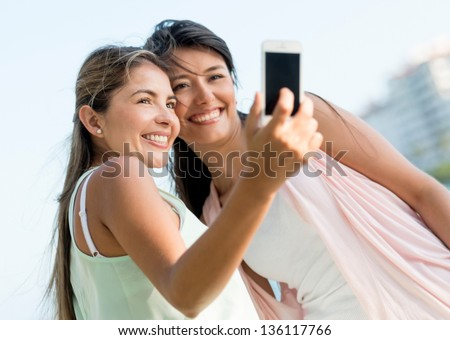 Happy friends taking a self portrait with a mobile phone - stock photo