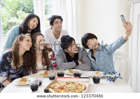 Happy friends taking photograph - stock photo