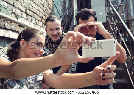 Happy friends taking self photo with smart phone. Selfie, friendship, young adult, happiness, leisure concept. Image toned. - stock photo