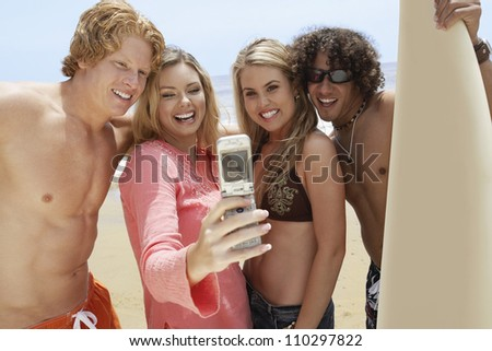Happy friends taking self-portrait through cell phone on beach