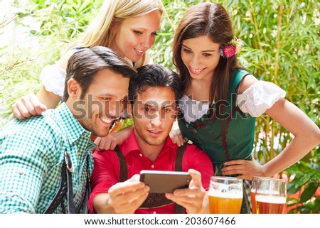 Happy friends taking selfie in bavarian beer garden in summer - stock photo