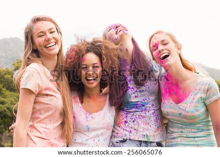 Happy friends throwing powder paint on a sunny day - stock photo