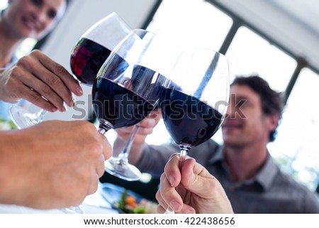Happy friends toasting wine glass while having lunch in restaurant - stock photo