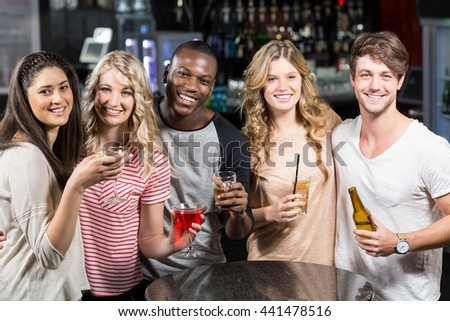 Happy friends toasting with beer and cocktails in a pub - stock photo