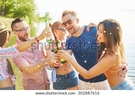 Happy friends toasting with bottles of beer - stock photo