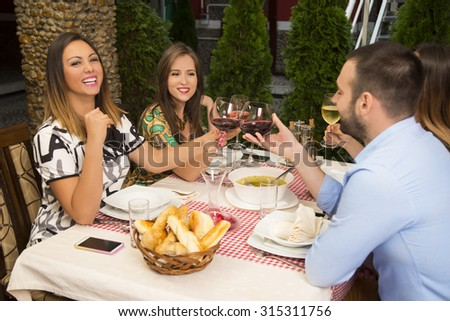 Happy friends toasting with wine and celebrating during a lunch in the restaurant. - stock photo