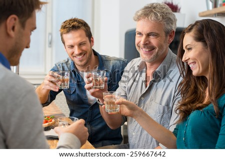 Happy friends toasting with wine glasses at home   - stock photo