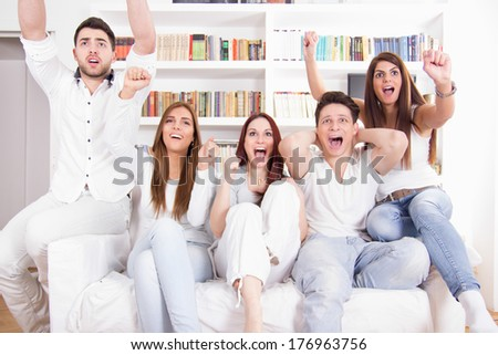 happy friends watching football match on tv cheering - stock photo
