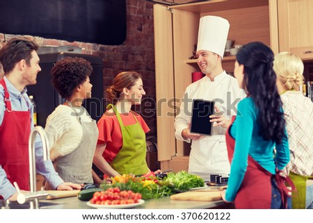 happy friends with chef and tablet pc in kitchen - stock photo