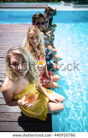 Happy friends with cocktail glass sitting side by side in swimming pool - stock photo