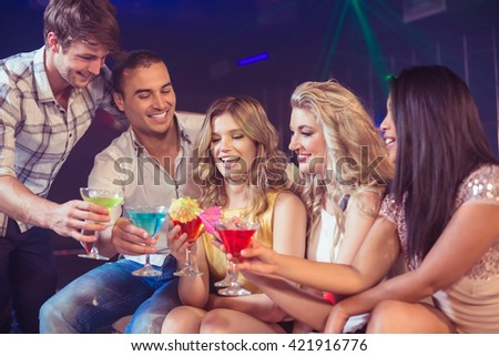 Happy friends with cocktails in a club