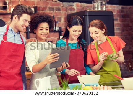 happy friends with tablet pc cooking in kitchen - stock photo