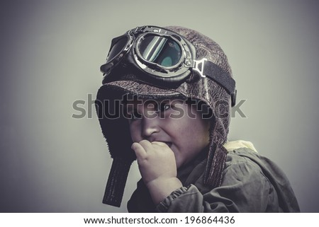 happy, fun and funny child dressed in aviator hat and goggles - stock photo