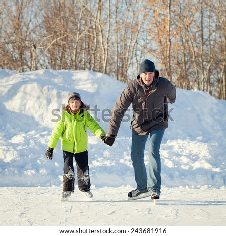 Happy fun father and son learning to skate, winter, outdoor - stock photo