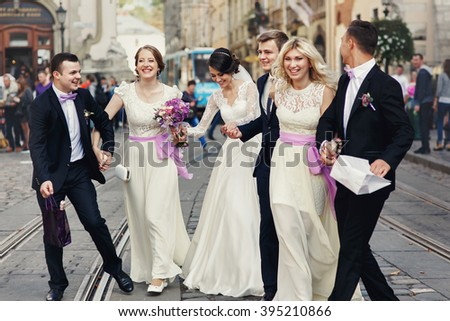Happy fun newlyweds posing in street with bridesmaids & groomsmen