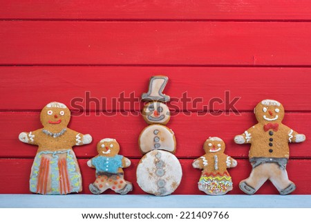 Happy funny gingerbread man family on wooden background with Snowman - stock photo