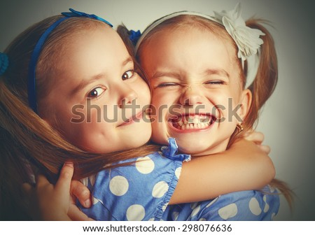 Happy funny girl twins sisters hugging and laughing - stock photo
