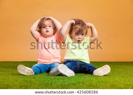 Happy funny girl twins sisters playing and laughing - stock photo