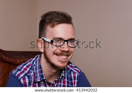 Happy funny guy sit ob chair and smile. Hipster with glasses asn beard have happy emotion. - stock photo