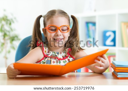 Happy funny kid girl in eyeglasses reading a book