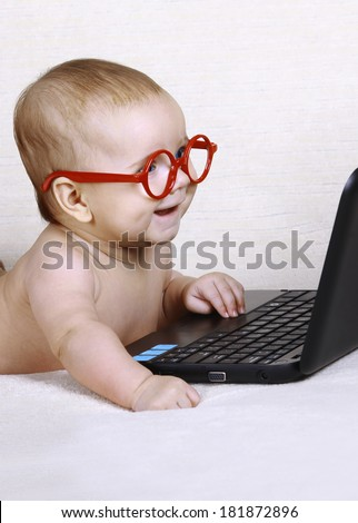 Happy funny kid with glasses is working at the computer - stock photo