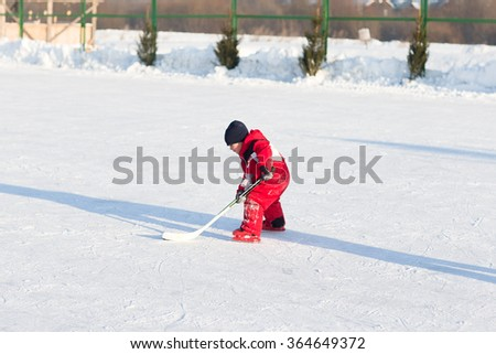 Happy funny kids playing hockey at the rink in the winter. A child with a stick on the ice skating in the winter walks on the street. - stock photo