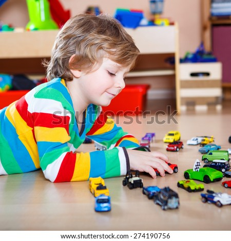 Happy funny little blond child playing with lots of toy cars indoor. Kid boy wearing colorful shirt and having fun at nursery. - stock photo
