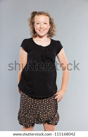 Happy funny teenage girl with curly blonde hair. Expressive face. Studio shot isolated on grey background. - stock photo