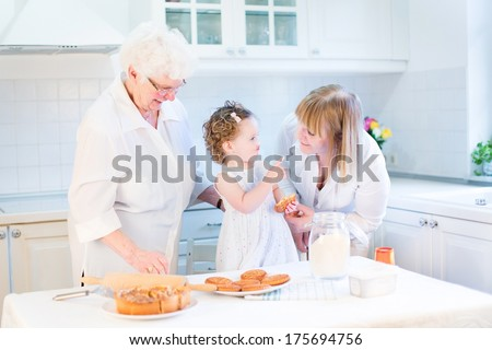 Happy funny toddler girl playing in a white beautiful kitchen baking an apple pie with her grandmothers - stock photo
