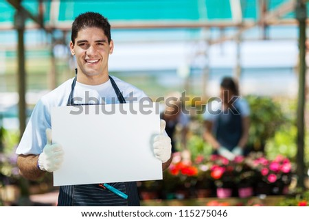 happy gardener holding white board in greenhouse - stock photo