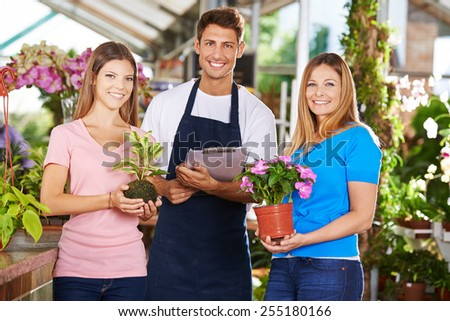 Happy gardener team group in nursery shop with plants and flowers - stock photo
