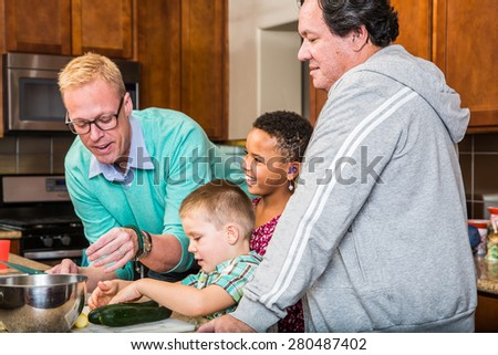 Happy gay dads with their children in the kitchen - stock photo