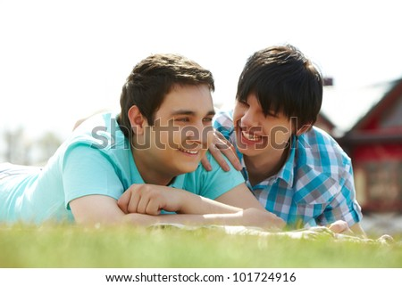 Happy gay lovers lying on the lawn - stock photo
