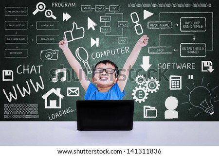 Happy geek boy winning computer science competition using laptop in class - stock photo