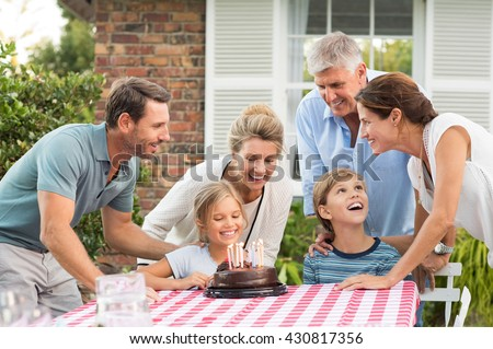 Happy generation family enjoying daughter surprise birthday party. Brother excited for birthday party. Happy young girl celebrating birthday party with family. - stock photo