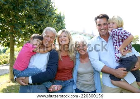 Happy 3 generation family in grandparents' backyard - stock photo
